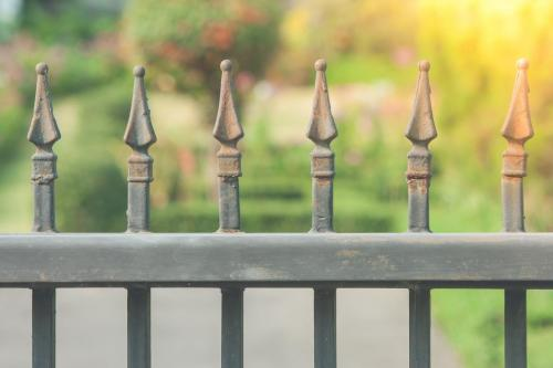 Close up cast iron fence or metal fence at the entrance with green garden and sunlight in the background. (Selective focus)